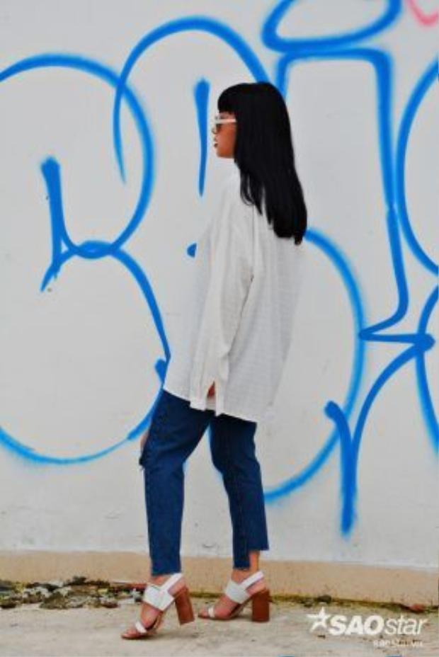 Cô nàng phối quần jean cắt gấu cùng áo sơ mi oversize và giày đế vuông.