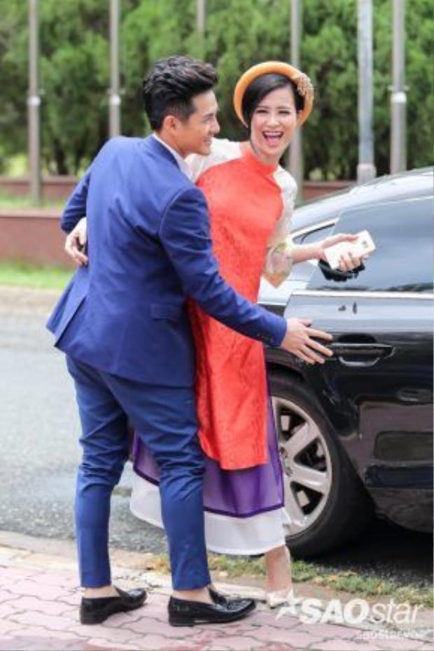 Vừa đến nơi, anh chàng đã vội vã xuống xe để mở cửa hộ bạn gái. Đông Nhi diện áo dài, khăn đóng màu cam nổi bật.