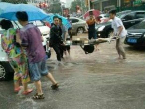 Bé gái bị nước xô ngã kẹt dưới gầm ôtô và ngạt nước tử vong. Ảnh: Shanghaiist.