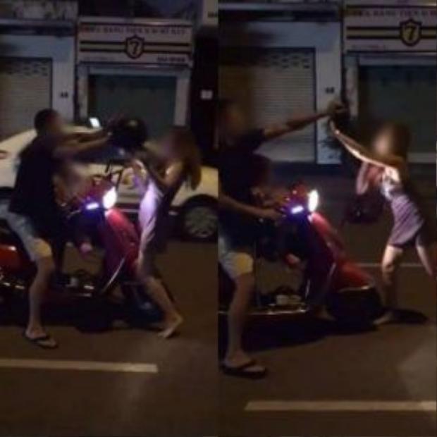 Người vợ dùng mũ bảo hiểm đanh liên tiếp về phía người chồng, mặc cho con gái nhỏ ngồi ngay phía trước. Ảnh cắt từ clip.