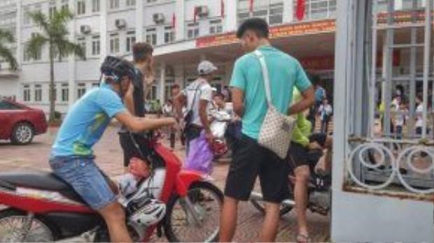Một nhóm học sinh di chuyển từ Hà Đông đến địa điểm thi phải đứng ở ngoài cổng trường. Ảnh: Nguyễn Sương.