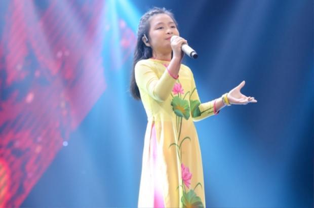 Nguyễn Hoàng Mai Anh trong bộ áo dài truyền thống tự tin thể hiện phần thi Tàu anh qua núi tại vòng GIấu mặt.