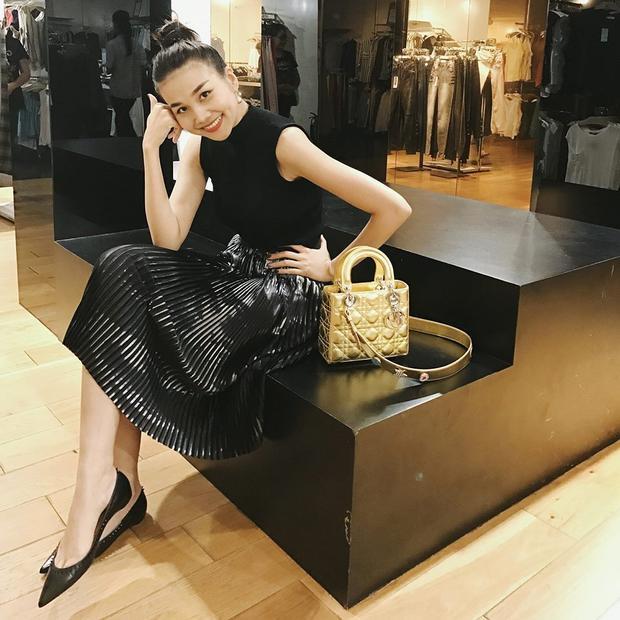 """""""Đàn chị"""" Thanh Hằng lại chọn outfit đơn giản và không quá màu mè gồm áo sát nách màu đen cùng váy pleat vải satin. Chiếc túi Dior màu vàng đồng đóng vai trò làm điểm nhấn hoàn hảo cho cả set đồ."""