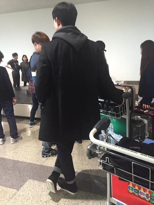 Taecyeon đứng đợi lấy hành lý.