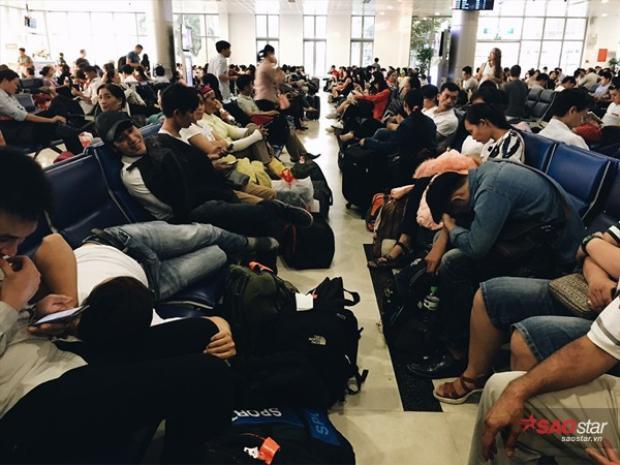 Trong phòng chờ ra cửa máy bay chật kín hành khách.
