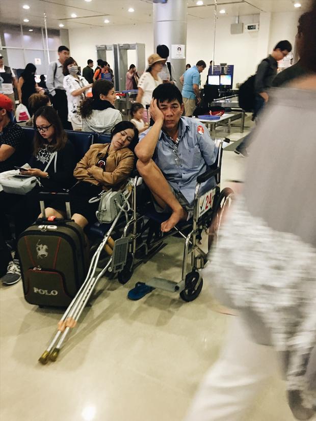 Vẻ mặt mệt mỏi của một người đàn ông khuyết tật trong lúc chờ lên tàu bay.
