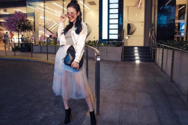Trước đó không lâu, cô nàng khoe street style siêu chất với áo khoác bomber chất liệu satin mix cùng chân váy sheer bồng bềnh ngọt ngào. Hoàn thiện set đồ là các phụ kiện: kính Gentle Monster, vòng choker, ankle boots và clutch đính nơ