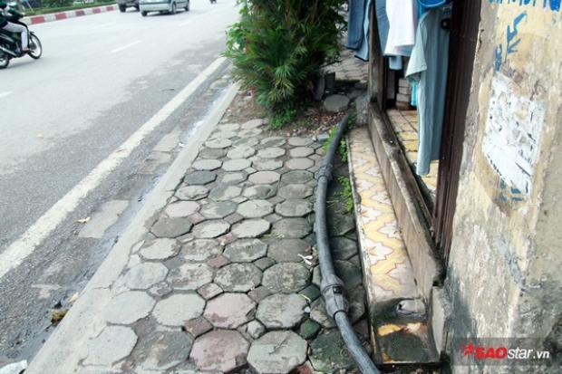 Đường ống nước chạy loằng ngoằng trước của nhà và trên vỉa hè.
