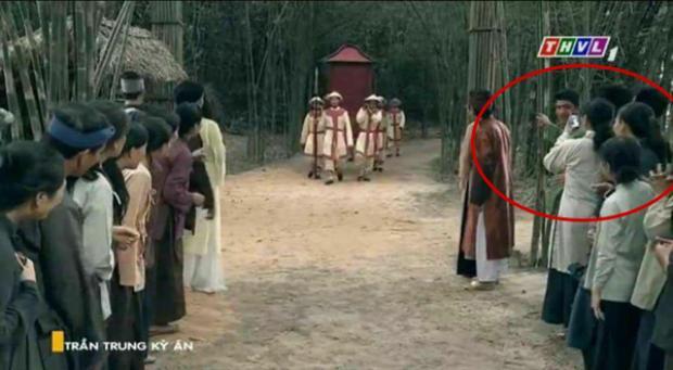Một diễn viên quần chúng giơ điện thoại smart phone ghi lại cảnh binh lính trong phim.