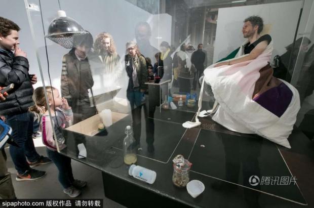 Nghệ sĩ người Pháp Abraham Poincheval đang thử nghiệm ấp trứng gà trong bảo tàng Palais de Tokyo.