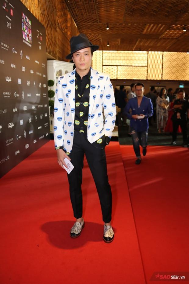 Nam người mẫu Lương Mạnh Hải trẻ trung với áo vest trắng họa tiết xanh biển đáng yêu. Tuy nhiên, áo gile được mix bên trong màu đen với chất liệu bóng lại khiến set đồ kém duyên hơn.