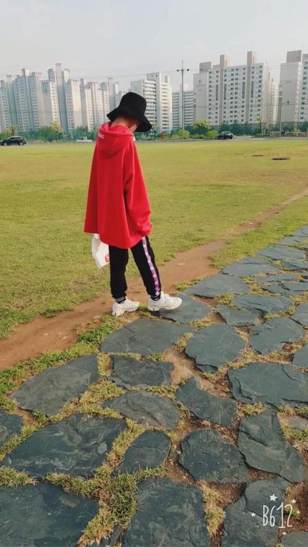 """Outfit của một thành viên Hàn Quốc trong hội. Cậu bạn """"chơi"""" mũ bucket và áo hoodie, quần jogger trong hai sắc đỏ - đen."""