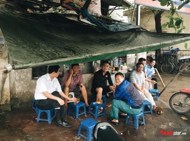 Một vài người đàn ông đang ngồi bên quán nước trà vỉa hè hưởng thụ tiết trời mát mẻ.
