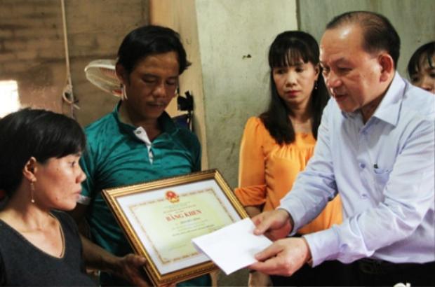 Ông Hà Hữu Phúc (phải), đại diện Bộ Giáo dục và Đào tạo trao bằng khen cho gia đình em Trần Đức Đông. Ảnh: Mạnh Tùng