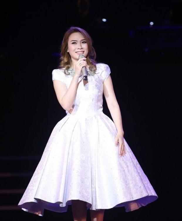 Cô xuất hiện với váy trắng tinh khôi cùng kiểu tóc uốn xoăn quen thuộc.