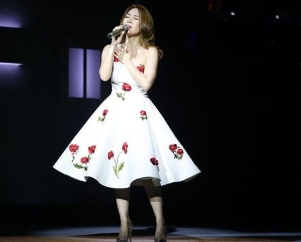 Cũng với phom dáng váy xòe, nữ ca sĩ trẻ trung và tươi mới hơn với sắc đỏ được nhấn nhá đầy tinh tế.