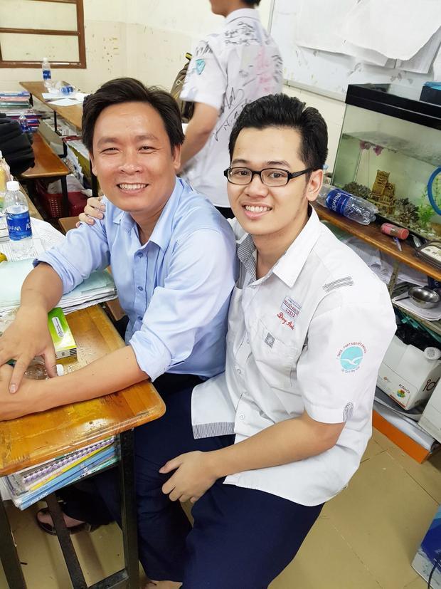 Cậu bạn tươi cười bên thầy giáo của mình trong tiết học cuối cùng.