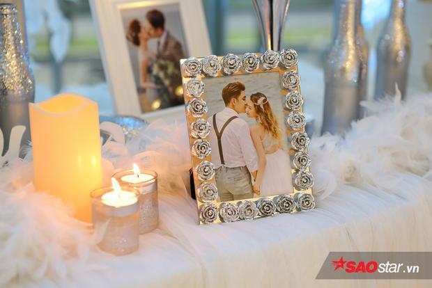 Bàn tiếp khách được trang trí bởi những khung ảnh hình cô dâu chú rể, điểm tô thêm là ánh nên lung linh, mờ ảo.