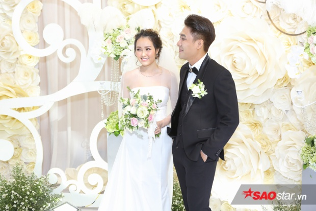 Huy Nam lịch lãm trong bộ vest đen cá tính, sánh đôi bên cô dâu Hiền Vy tinh khôi trong bộ áo cưới màu trắng đơn giản.