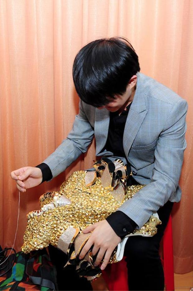 Trong một lần tháp tùng Đông Nhi đi diễn, Ông Cao Thắng không ngần ngại ngồi khâu trang phục cho bạn gái khi cô gặp sự cố.