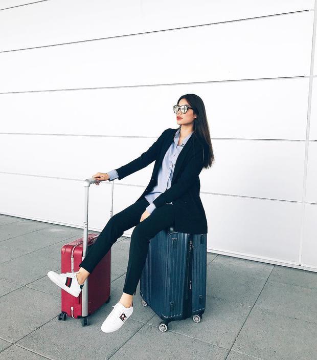 """Dù trên đường ra sân bay, hoa hậu """"ong chúa"""" vẫn theo đuổi hình tượng """"soái ca"""" trong bộ suit đen kết hợp cùng giày sneaker Gucci."""