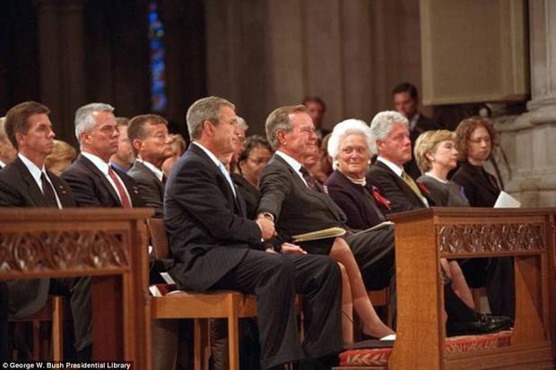 Cựu Tổng thống George W. Bush nắm chặt tay cha, cựu Tổng thống George H.W.Bush trong buổi lễ cầu nguyện và tưởng niệm quốc gia. Xa Xa, Tổng thống BIll Clinton cùng vợ và con gái cũng có mặt.