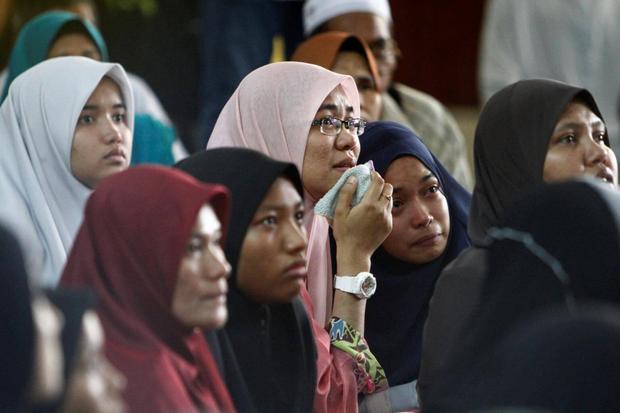 Các thành viên trong gia đình chờ đợi tin tức của những người thân yêu bên ngoài trường tôn giáo Darul Quran Ittifaqiyah sau khi ngọn lửa bùng phát.