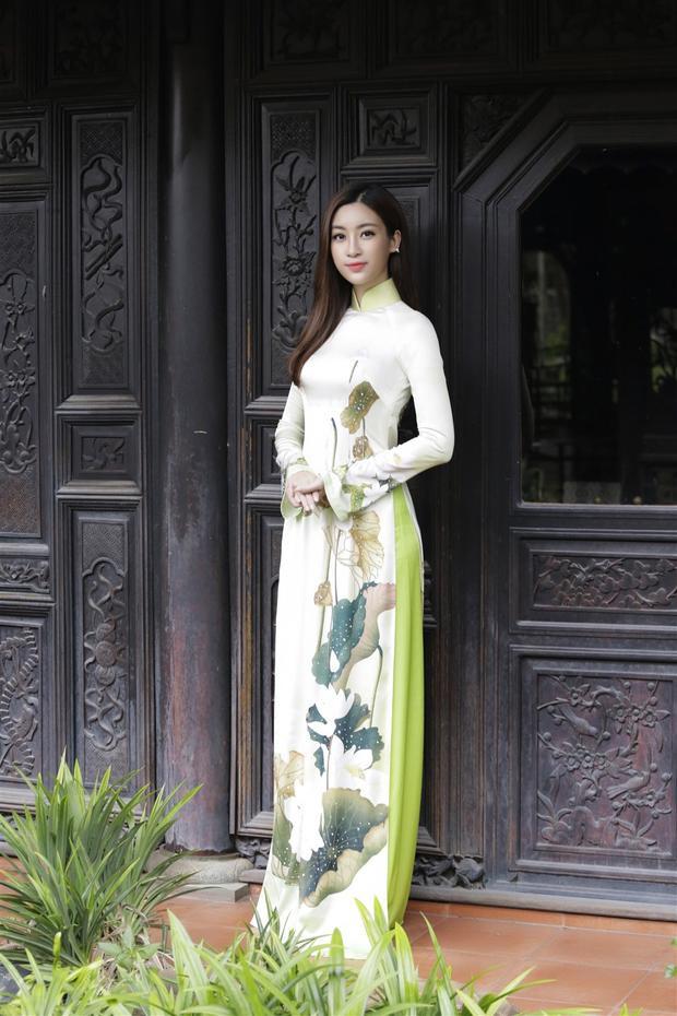Hoa hậu Mỹ Linh diện chiếc áo dài trắng với những họa tiết thanh tao ngồi bên cây đàn bầu.