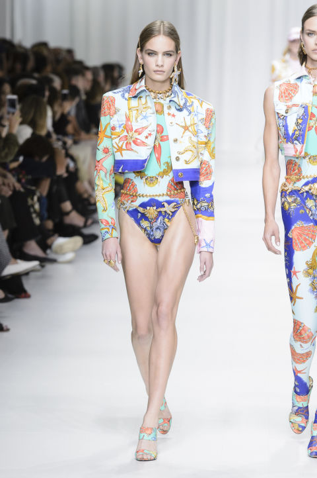 """Thế nhưng thay vì sử dụng phụ kiện đi kèm là những đôi boots hầm hố thì Versace lại chú trọng đến sự nữ tính của thiết kế bằng mẫu giày cao gót tiệp với các bộ cánh. Chưa kể, việc lựa chọn phụ kiện """"mát tay"""" cũng là điểm cộng hoàn hảo khiến giới điệu mộ đánh giá cao nhà mốt này."""