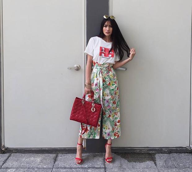 Quần hoạ tiết hoa mùa hè nhiều màu sắc phối ăn ý cùng áo thun trắng. Phụ kiện túi xách và giày đồng màu làm điểm nhấn cho hình ảnh năng động, trẻ trung.