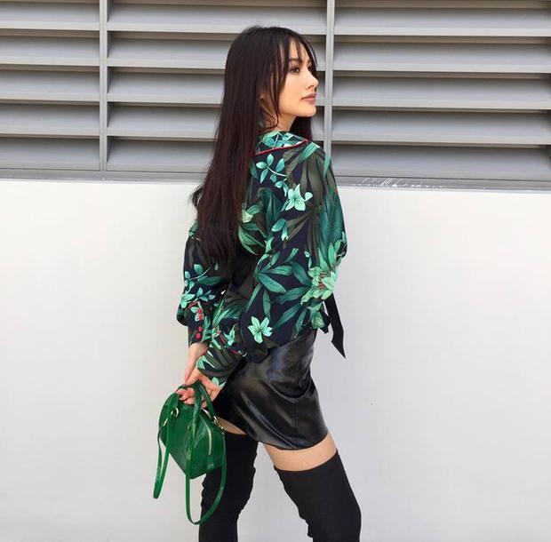 Áo voan hoạ tiết hoa kém người mặc được diễn viên xinh đẹp phối ăn ý cùng chân váy da, boots cao cổ và túi xách màu xanh lục.