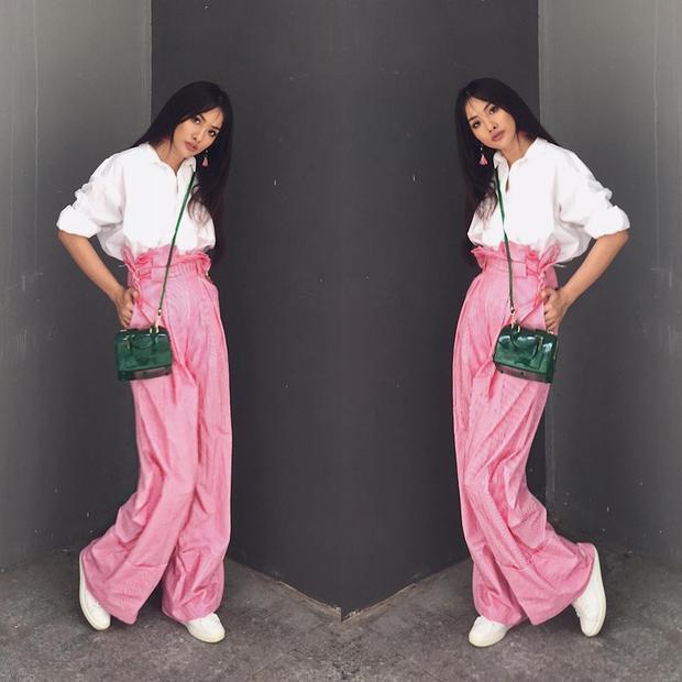 Quần lụa tông hồng kén người mặc được nữ diễn viên phối hoà hợp cùng sơ-mi trắng, hoa tai ton sur ton gam hồng. Phụ kiện túi xách đeo chéo tông xanh lục làm điểm hút ánh nhìn.