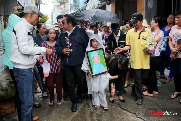 Con nuôi của nghệ sĩ Khánh Nam - bé Khánh Nhi bần thần ôm di ảnh bố.