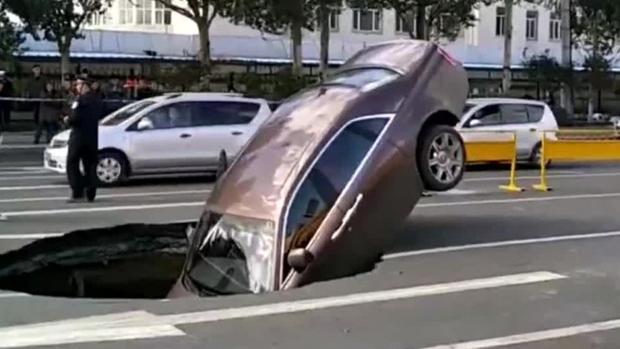 Chiếc xe sang lao thẳng xuống hố tử thần trên mặt đường. Ảnh: SCMP