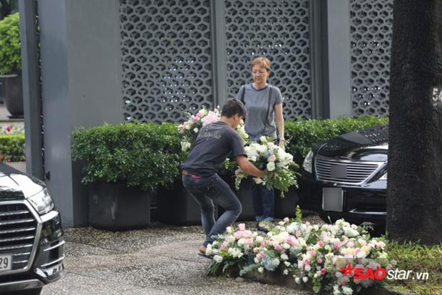 Hoa tươi đang được chuyển đến và sắp xếp, trang trí trước nhà chú rể Trung Tín.