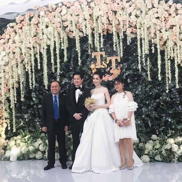 Ở thời điểm đón khách mời, Hoa hậu diện đầm cưới sắc trắng. Thiết kế được nhấn nhá ren trắng tinh tế ở vai áo. Chân váy xếp gấp thành đường ly lớn tạo điểm nhấn cho bộ đầm phong cách công chúa cổ tích.