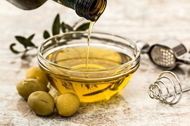 """Dầu ô liu loại extra virgin: Dầu ô liu là một chất béo có lợi cho sức khỏe giúp loại bỏ chất béo """"xấu"""" (bão hòa) trong khi giảm lượng cortisol ảnh hưởng đến tăng cân. Tuy nhiên, dầu ô liu sẽ mất hầu hết các tác dụng nếu bị đun nóng, vì vậy hãy ăn một thìa dầu ô liu sống ngay khi bụng đói. Hoặc, nếu bạn không thích, hãy thêm dầu ô liu vào salad hoặc món súp của bạn."""