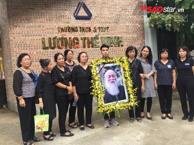 Cựu học sinh mang theo di ảnh của thầy Cương đến chờ xe linh cữu đi qua.