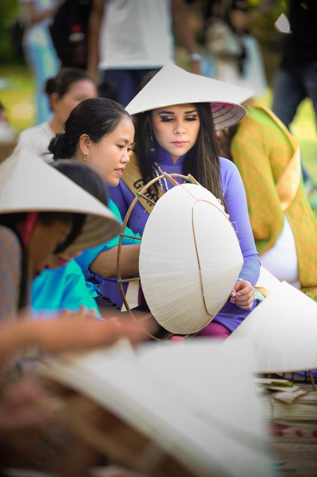 Miss Grand Guatemala chăm chú theo dõi nghệ dân làm nón lá.