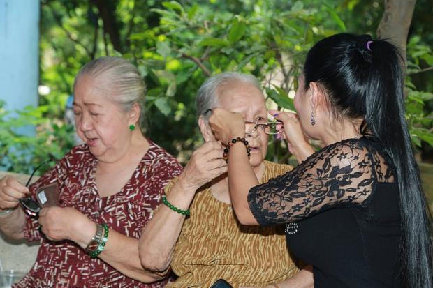 Ngọc Huyền ân cần chỉnh sửa lại kính cho một nghệ sĩ lớn tuổi.