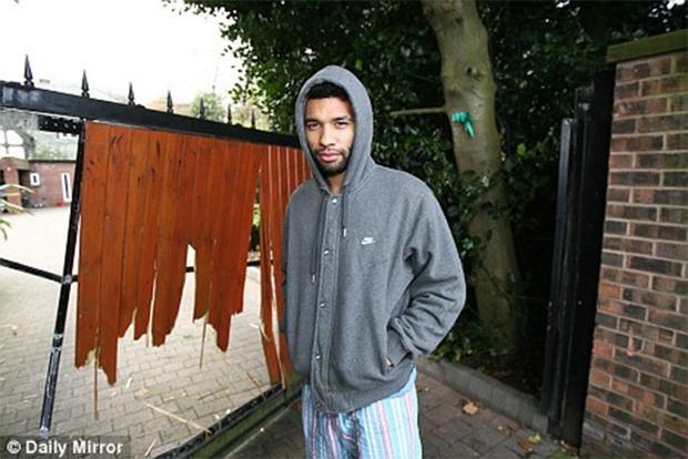 Cựu cầu thủ Liverpool Jermaine Pennant đứng bên chiếc cổng bị phá nát khi bọn trộm đào tẩu.
