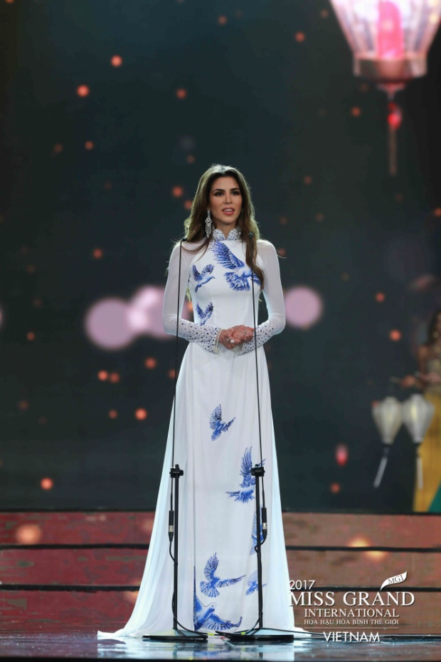Người đẹp Peru - thí sinh đăng quang Miss Grand 2017 trông thật sang trọng và thanh lịch trong tà áo dài trắng họa tiết chim bồ câu. Với chiều cao lý tưởng 1m8 cùng số đo ba vòng hoàn hảo 89 -60- 89, cô dễ dàng chinh phục mẫu áo dài với phần tà áo cùng ống quần rộng. Thần thái, biểu cảm, gương mặt sắc nét của Tân Hoa hậu Hòa bình Thế giới 2017 cũng được đánh giá là phù hợp khi diện trang phục truyền thống Việt Nam.