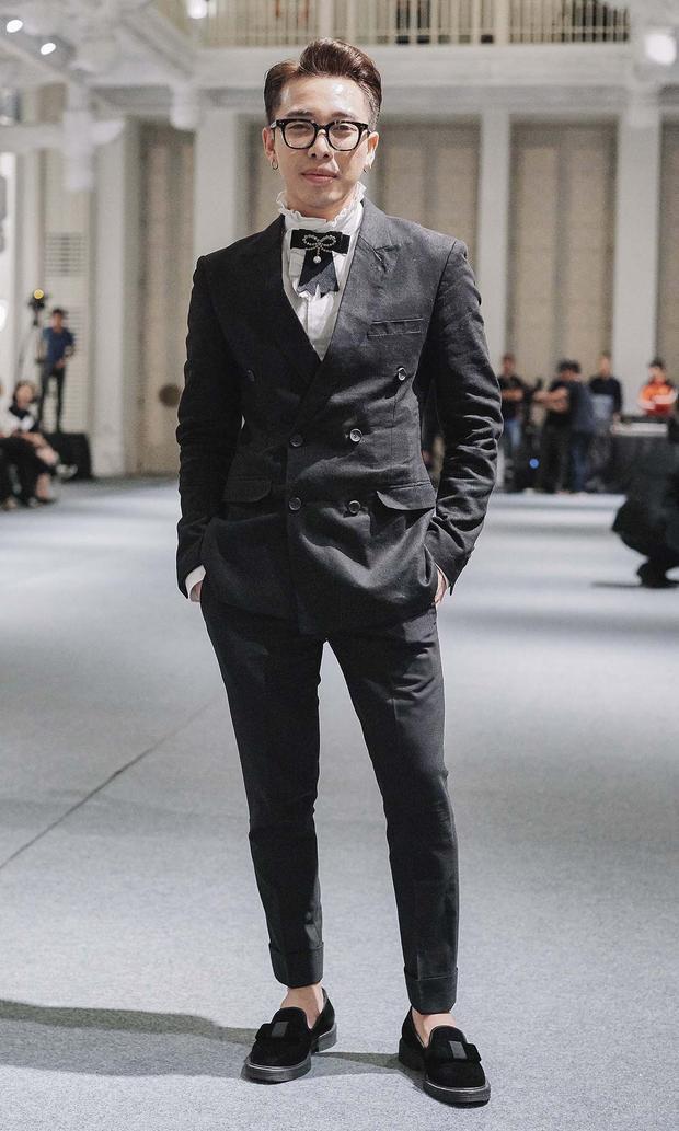 Stylist Hoàng Ku bảnh bao trong bộ vest đen, áo sơ-mi cổ điển đính nơ, giày nhung đồng màu tiệp cùng tổng thể.