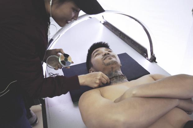 """Chuyên viên hóa trang đang chuẩn bị cho cảnh quay """"cắt đổi đầu người""""."""