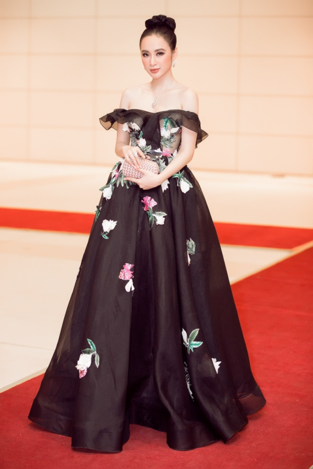 Diện mẫu váy dạ hội gam màu đen, với phần tùng đen xòe chất liệu voan thêu ruy băng họa tiết hoa trắng, kết hợp phần vai trễ ngang khoe trọn làn da trắng sứ. Diễn viên sinh năm 1995 thật sự nổi bật.