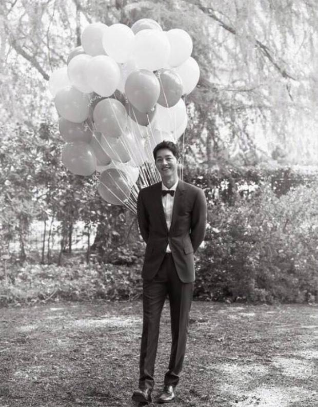 Song Joong Ki mỉm cười mãn nguyện, tay cầm bóng bay mắt hướng về phía cô dâu của mình.