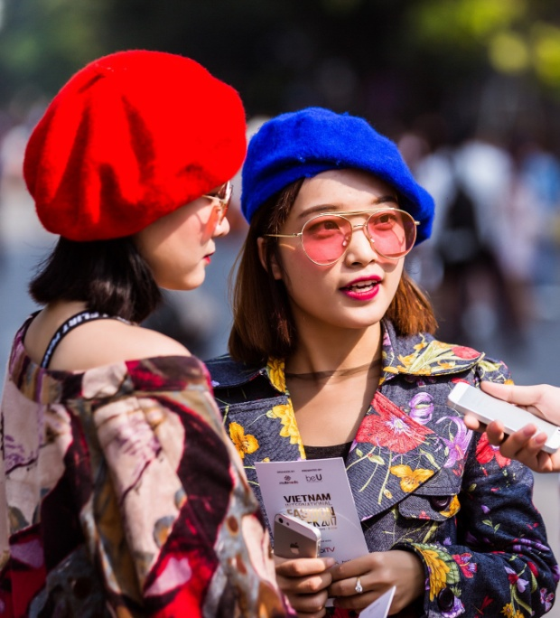 Hai cô bạn này thì lại nổi bật hết phần người khác với mũ nồi tông đỏ cùng xanh colban, đi kèm áo khoác hoa rực rỡ. Chi tiết kính mát màu sắc cũng là nhấn nhá rất hay cho set đồ thêm hoàn thiện.