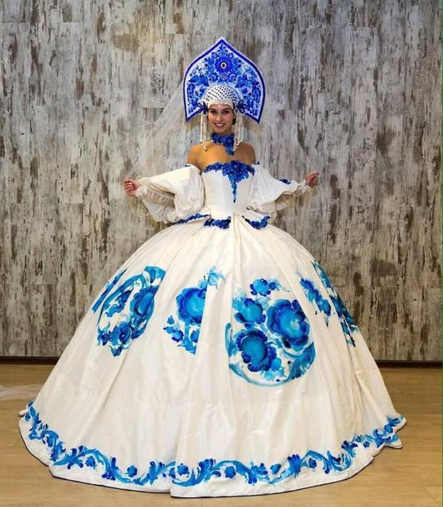 Đại diện Nga lựa chọn hình tượng búp bê Nga nổi tiếng cho trang phục truyền thống của mình. Thiết kế váy phồng nổi bật, họa tiết hoa sóng trắng, xanh đặc trưng của nước Nga, chiếc nón được thiết kế cầu kỳ tạo nên cái nhìn ấn tượng cho bộ quốc phục.