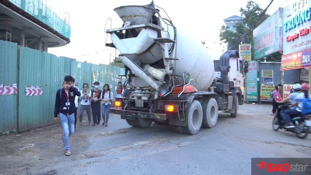 Xe tải chở vật liệu ra vào công trình gần khu vực các bạn buôn bán.