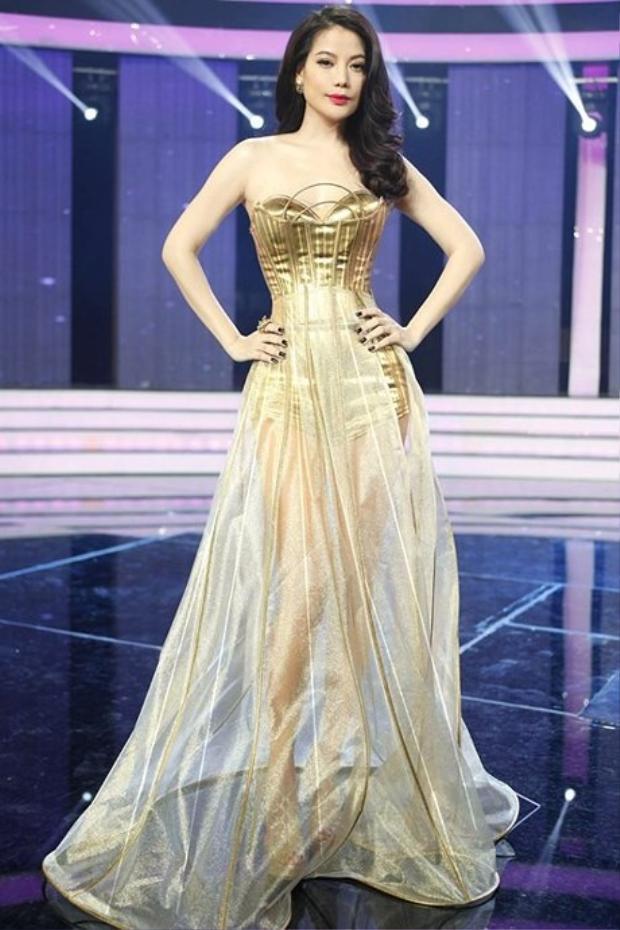 """Hay mẫu váy dạ hội tông màu vàng ánh kim lộng lẫy, chi tiết cúp ngực may gọng 3D tinh tế cùng chất liệu tùng váy xuyên thấu, có độ óng ánh tạo cho nàng Dần trong """"Áo lụa Hà Đông"""" sự nổi bật giữa sân khấu."""
